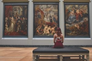 An art display is being observed by a woman.